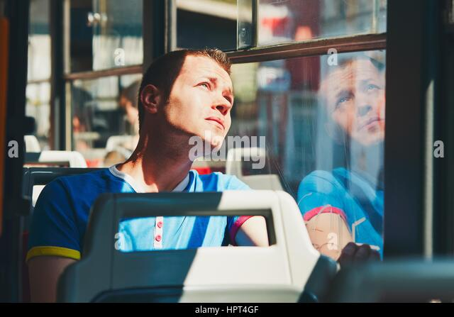 Everyday life and commuting to work by public transportation. Handsome young man is traveling by tram (bus). - Stock-Bilder
