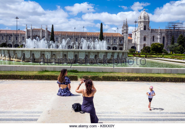 Portugal Lisbon Belem Praca do Imperio Empire Square park garden fountain woman girl child posing smartphone - Stock Image