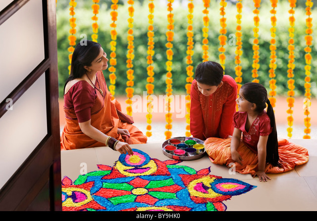Woman making a rangoli while her children watch - Stock Image