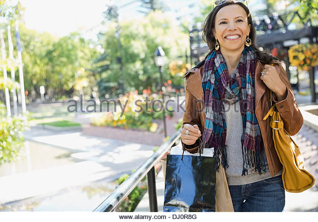 Woman with shopping bags walking outdoors - Stock Image