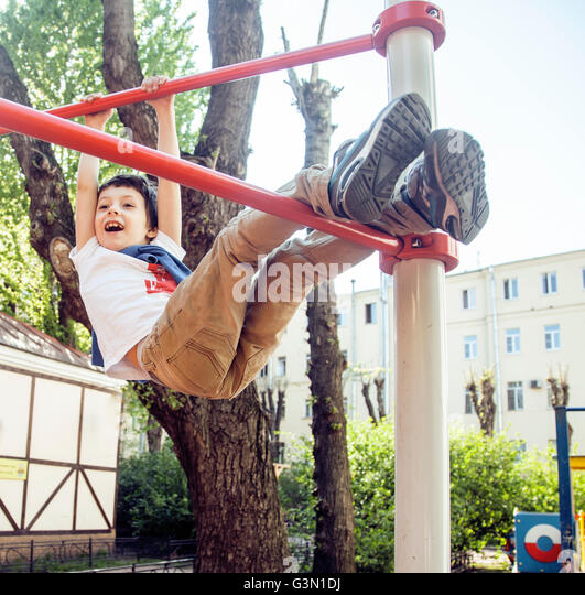 little cute blond boy hanging on playground outside, alone training with fun, lifestyle children concept - Stock Image
