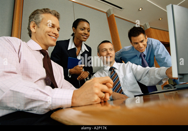 Businesspeople looking at computer monitor - Stock Image
