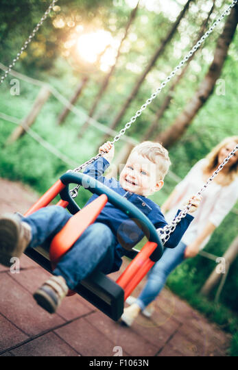 Mother and child outdoors in playground riding a  swing and smiling - Stock-Bilder