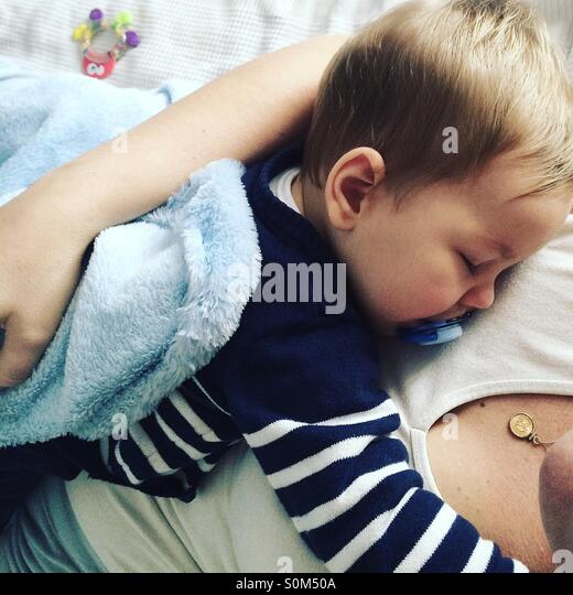 Tired 9 months old baby boy taking a nap on top of his mom . - Stock Image