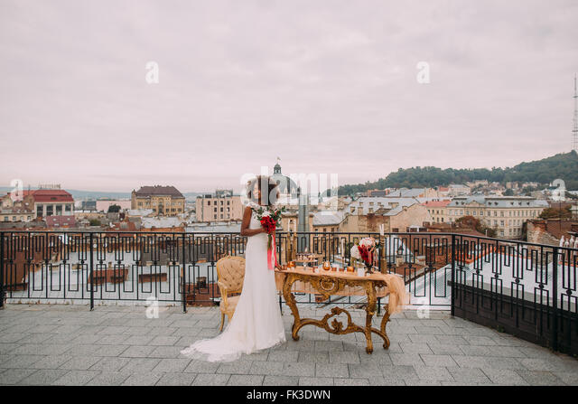 Pretty african bride with wedding bouquet in hands standing on the terrace - Stock-Bilder