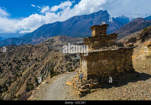 Tibetan prayer stupa or prayers place of the faithful Buddhists in center Mountains Path. Blue Sky Background. Horizontal - Stock Image