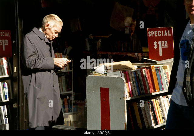 A browser engrossed in one of the books which are stacked on shelves marked with their bargain price tags in a second - Stock Image