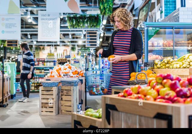 Woman buying oranges while carrying shopping basket in supermarket - Stock-Bilder