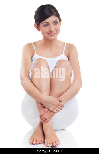 Smiling young woman rubbing her leg over white background - Stock-Bilder