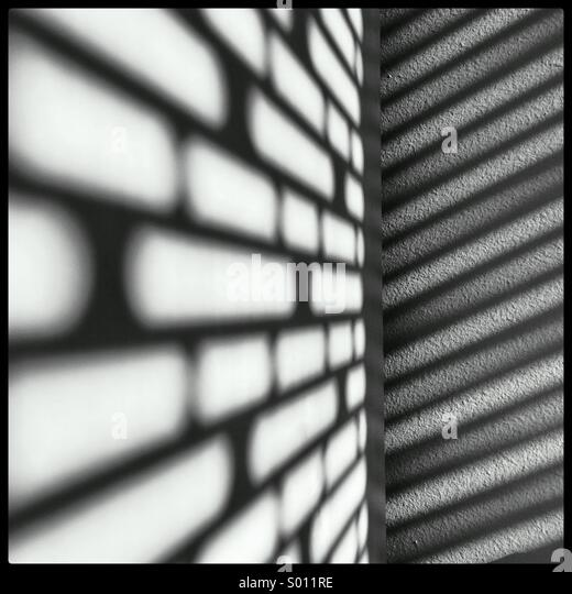 The sun casting cool shadows on my wall and bookshelf through the blinds in my office. - Stock Image