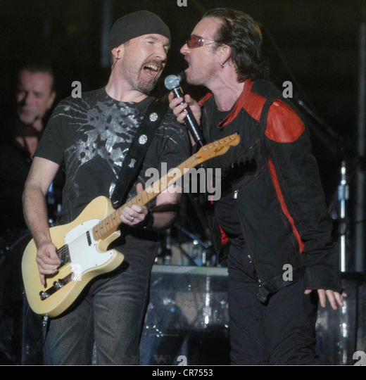 U2, Irish rock band, frontman Bono Vox is singing in the rain, half length, with guitarist The Edge, Olympic stadium, - Stock Image