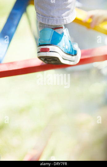 Child climbing on jungle gym, low section - Stock-Bilder