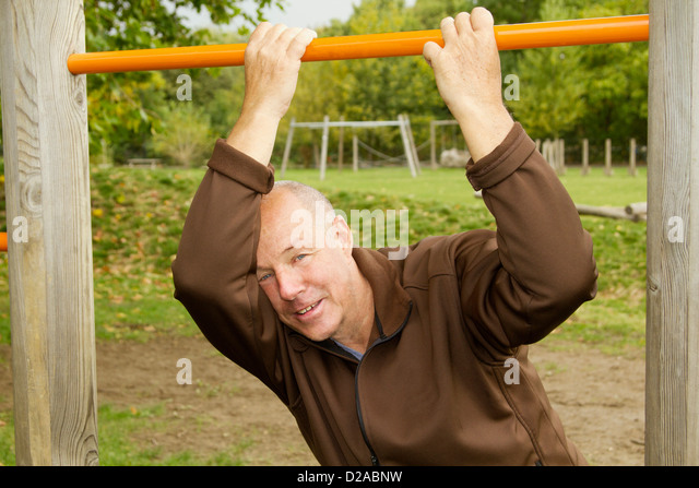 Older man hanging from jungle gym - Stock-Bilder