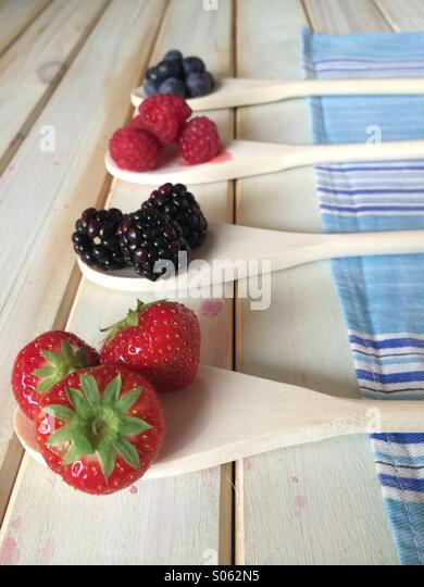 Strawberries blackberries and raspberries on wooden spoon - Stock Image