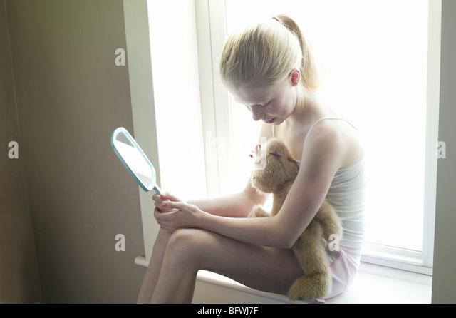 girl w teddy bear near window looking at mirror - Stock Image