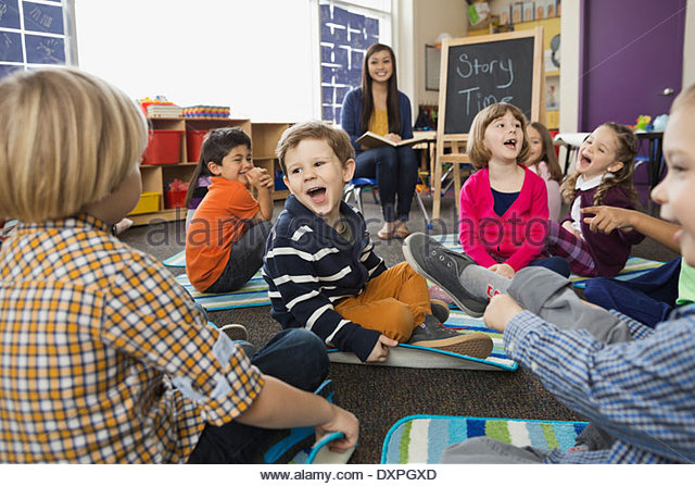 Cheerful students with teacher in elementary school during Story Time - Stock Image