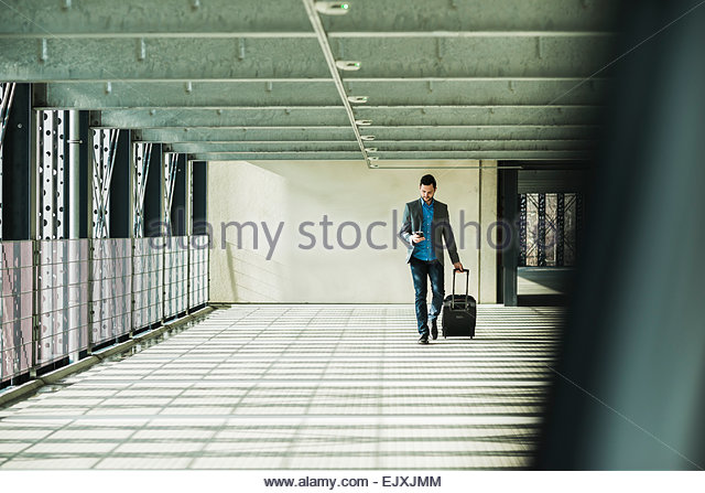 Young businessman walking in car park looking on cell phone - Stock Image