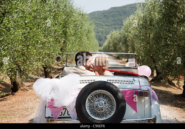 Newlyweds kissing in classic car - Stock Image
