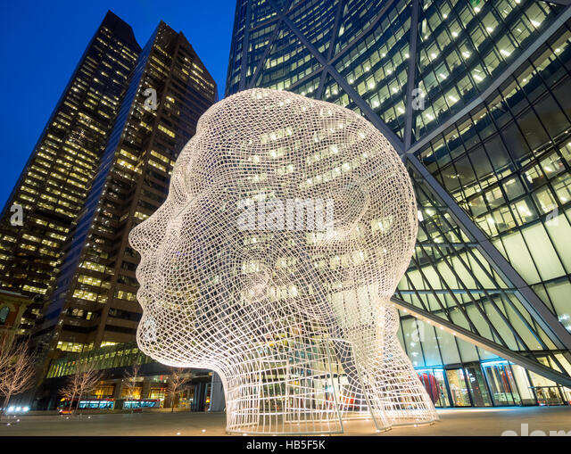 A night, fisheye view of the sculpture Wonderland by Jaume Plensa, in front of The Bow skyscraper in Calgary, Alberta, - Stock Image