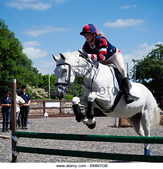Show jumping with a white horse in an equine arena. Teenage girl riding a white horse over a jump, UK. - Stock Image