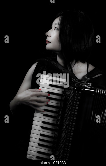 young woman playing accordion - Stock Image
