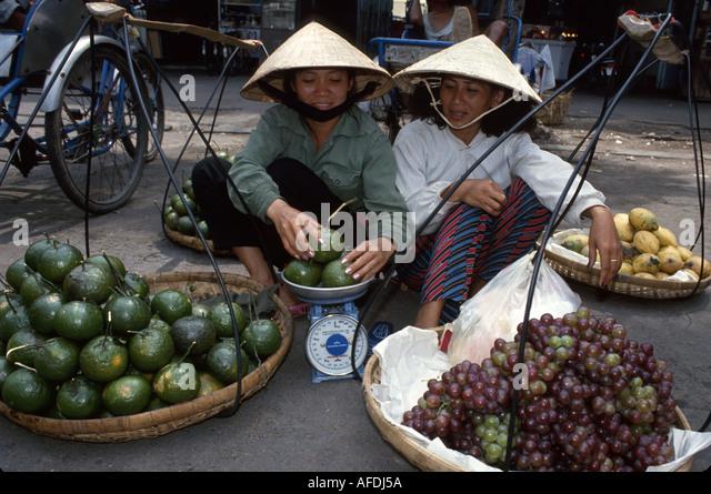 Vietnam Saigon Ho Chi Minh City Cho Ben Thanh Market female produce vendors scale grapes - Stock Image
