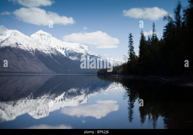 Snow capped mountains and sky reflected in water - Stock Image