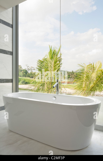 Modern ceramic bathtub and glass picture windows with view - Stock Image
