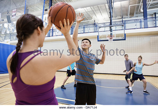 Men and women playing basketball in gym - Stock Image