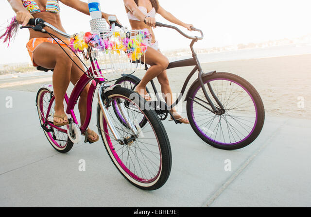 Neck down view of two women cyclists on beach, Mission Bay, San Diego, California, USA - Stock-Bilder