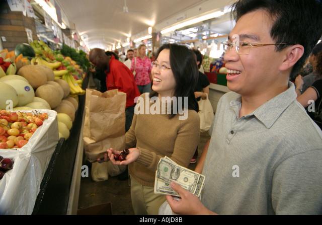 Cleveland Ohio Westside Market produce food fruits vegetables cherries Asian man woman couple shoppers money buying - Stock Image