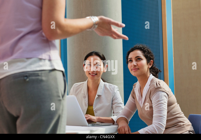 Office workers using laptop and looking at colleague - Stock Image
