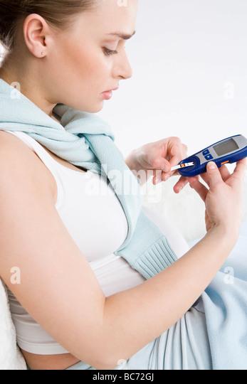 pregnant woman making blood sugar test - Stock Image