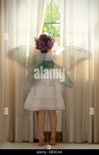 Girl wearing fairy costume looking out of window - Stock Image