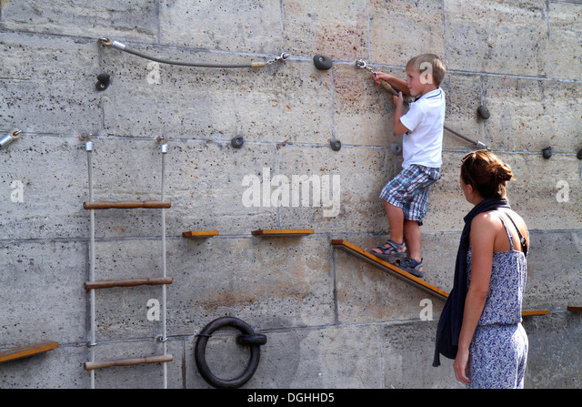 Paris France Europe French Seine River La Rive Gauche Left Bank Berges de Seine climbing wall boy mother physical - Stock Image