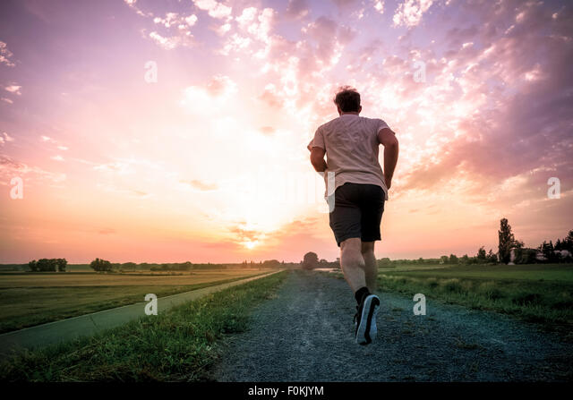 Rear view of man jogging at sunset - Stock-Bilder
