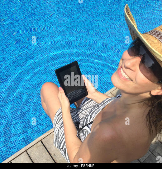 Smiling woman with digital tablet sitting at the edge of swimming pool - Stock Image