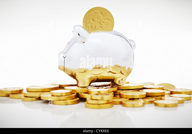 Stack of gold coins by piggy bank - Stock Image