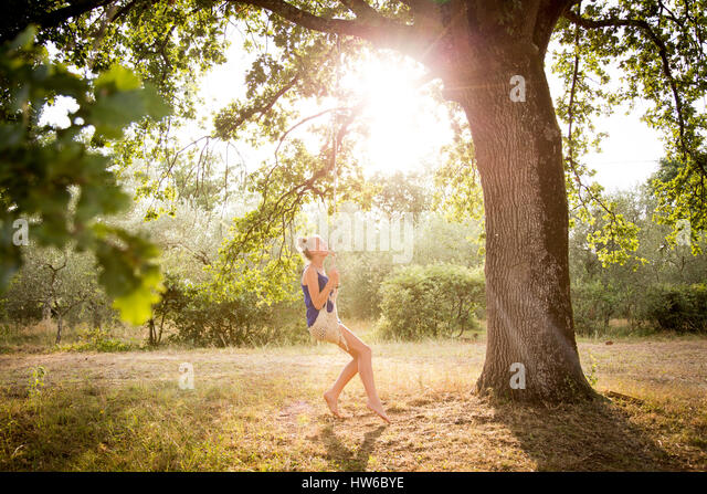 Girl in Italy on a swing in the backyard - Stock Image