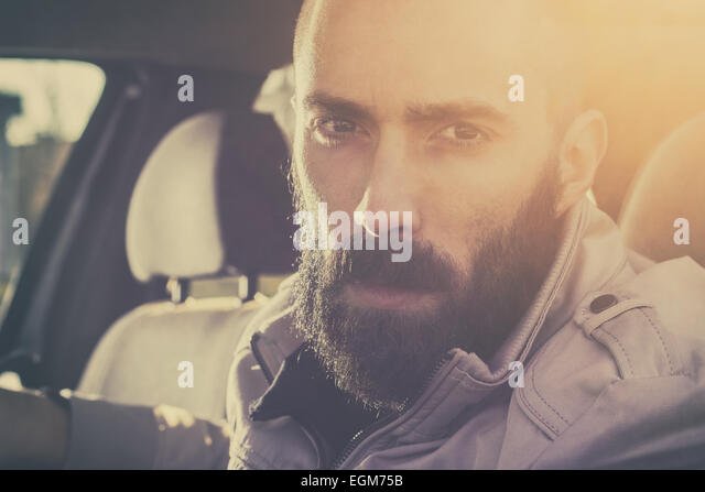 Young handsome man driving his car on a beautiful sunny day. Retro tones. - Stock-Bilder