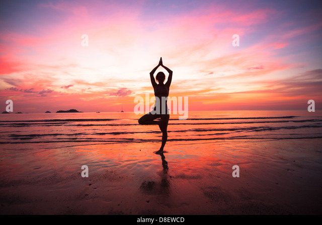 Young woman yoga practice at the seaside at sunset. - Stock Image