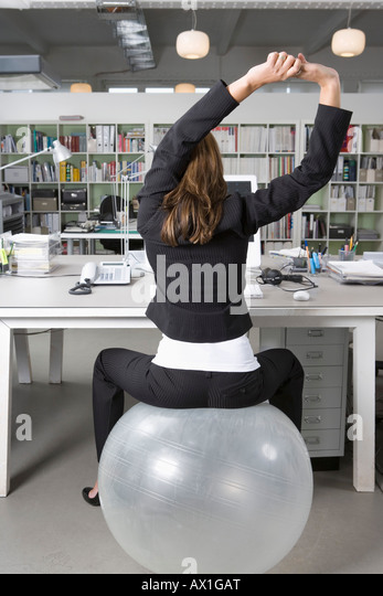 a-woman-sitting-on-an-exercise-ball-at-a