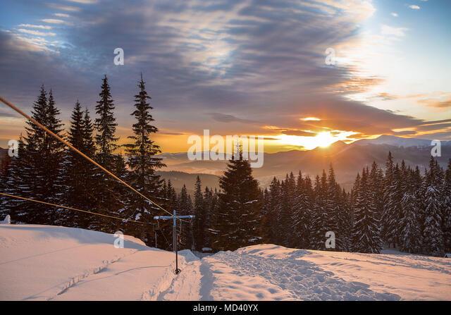 Ski lift on snow covered landscape at sunset, Gurne, Ukraine, Eastern Europe - Stock Image