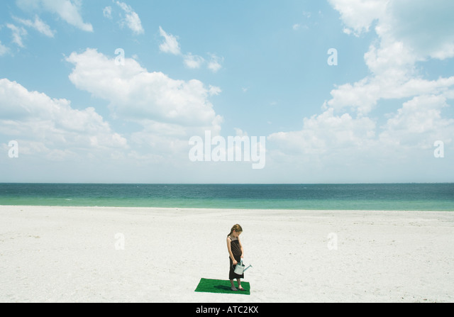 Girl standing on square of artificial turf on beach, holding watering can, high angle view - Stock Image