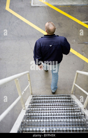 Man going down metal stairs - Stock Image