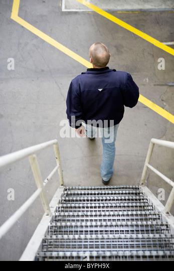 Man going down metal stairs - Stock Image