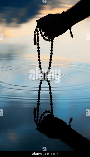 Hand holding Indian Rudraksha / Japa Mala prayer beads over rippling water . Silhouette - Stock-Bilder