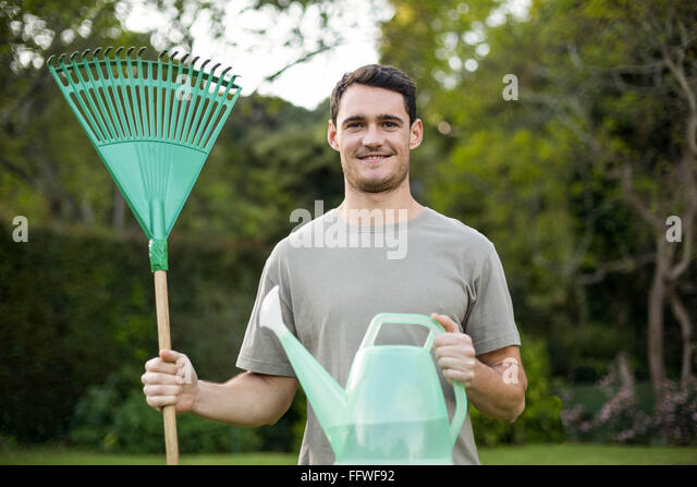 Portrait of young man standing with a gardening rake and watering can - Stock Image