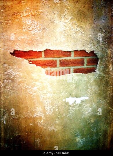 Brick wall behind a concrete front - Stock Image