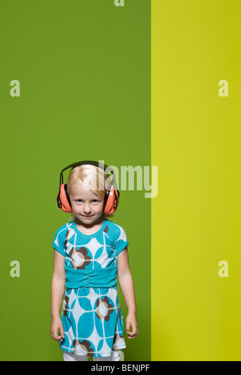 Little girl wearing protective headphones - Stock Image